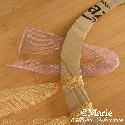 Tulle netting strips starting to tie around a cardboard base