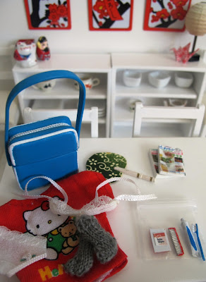 Modern dolls' house miniature dining table with a carry on bag, toiletries and spare underwear on it.