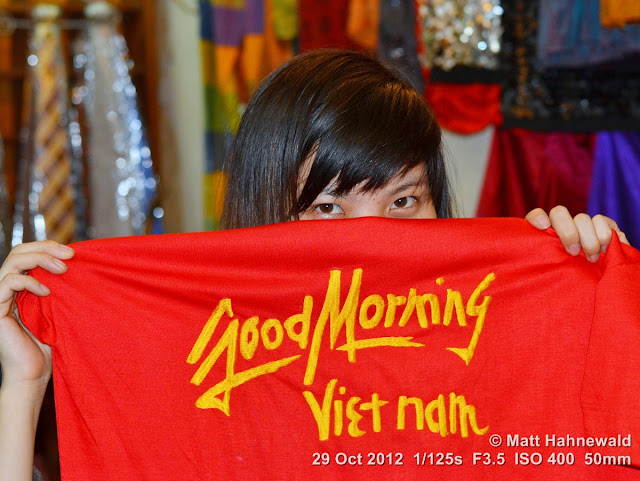 people, street portrait, headshot, face, eyes, eye contact, Vietnam, Hanoi, saleslady, hiding, T shirt, Good Morning Vietnam