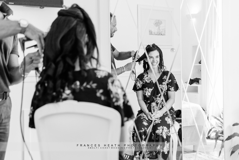 Bride having hair done on wedding day