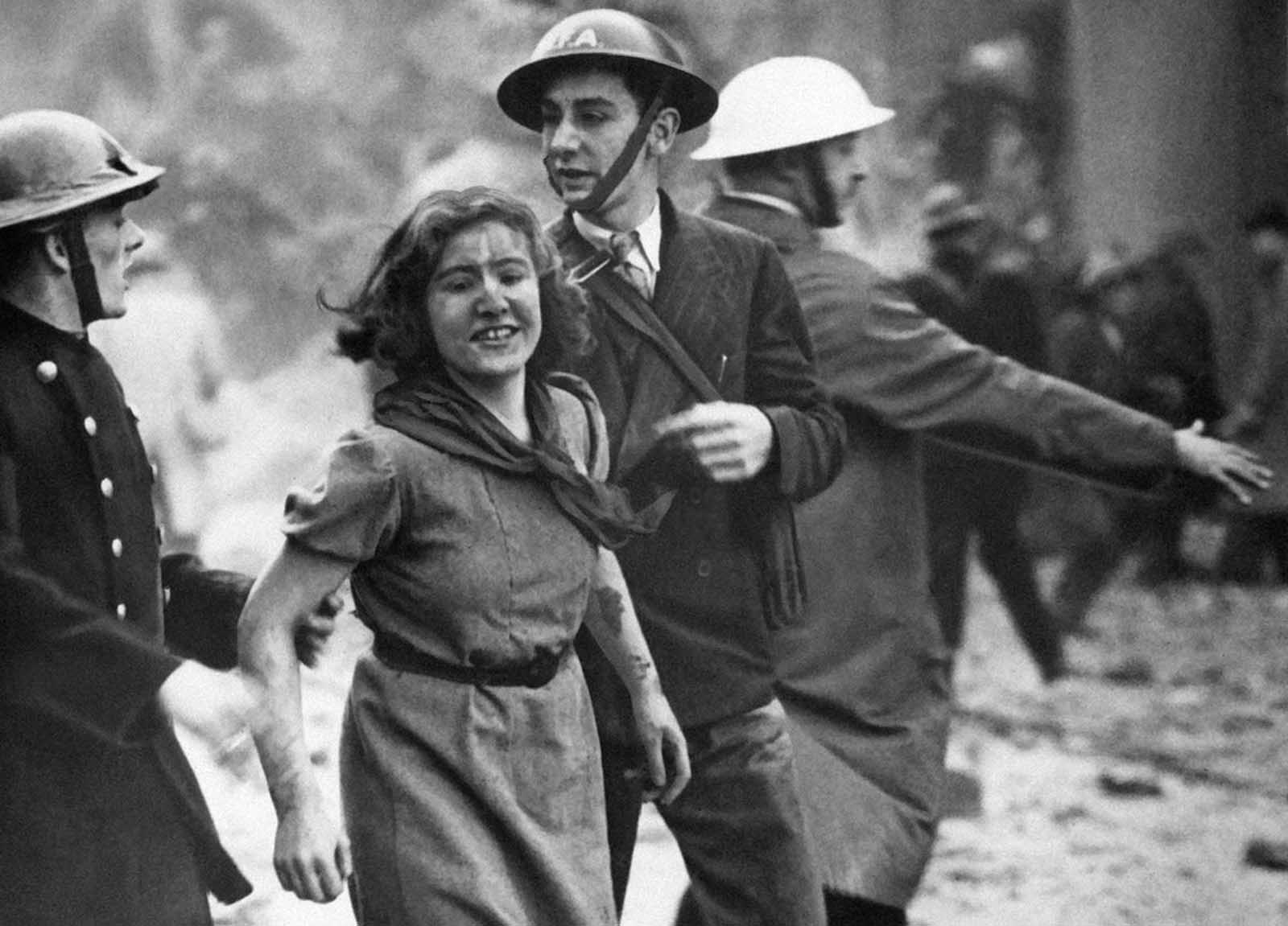 This smiling girl, dirtied but apparently not injured, was assisted across a London street on October 23, 1940, after she was rescued from the debris of a building damaged by a bomb attack in a German daylight raid.