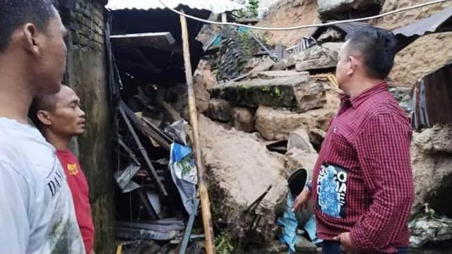Warga menyaksikan rumah yang rusak akibat terkena tanah longsor di Sibolga.
