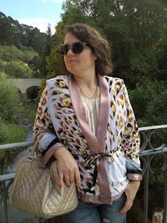 Casaco de fundo branco e padrão animal, com barra rosa nas mangas, fundo e decote. Apertado com atilho à cintura