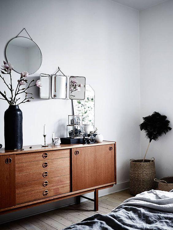 Une commode en bois, des fleurs et des miroirs pour habiller la chambre