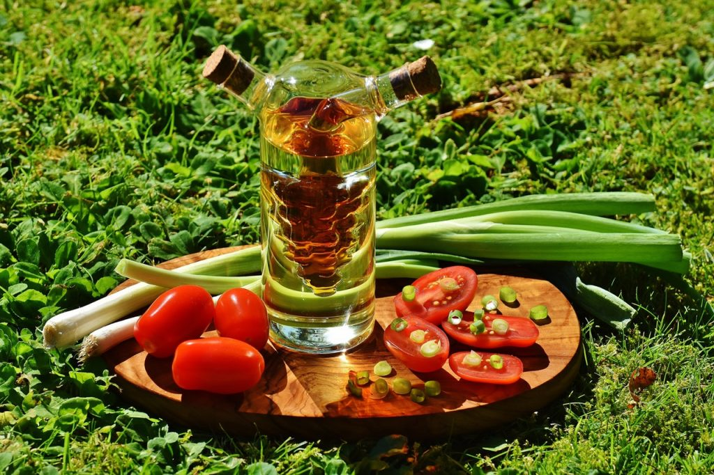 Salad platter with spring onions, tomatoes and a glass container of oil