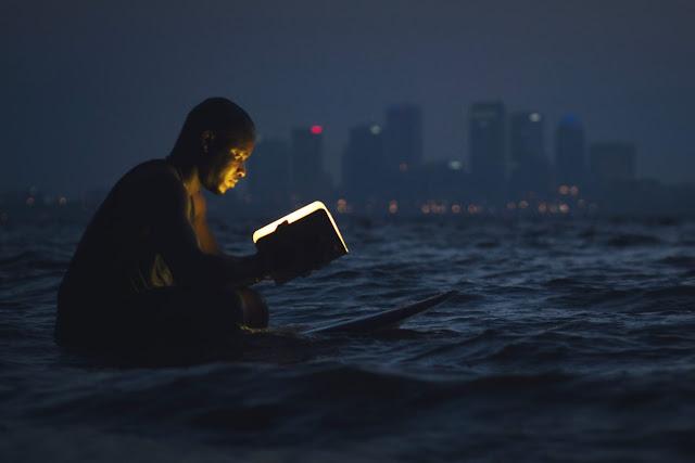 Hombre leyendo en el mar