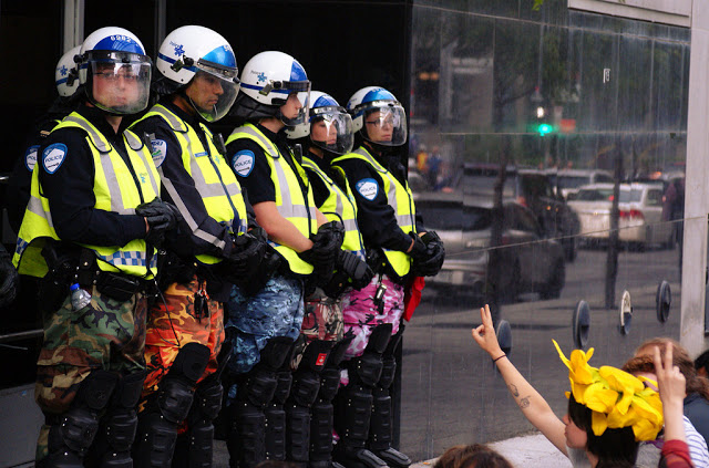 Montreal Police in riot gear wearing colorful camo pants. Police Pants Protest. marchmatron.com