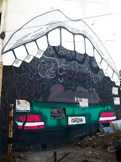 Street art of a huge mouth engulfing a car