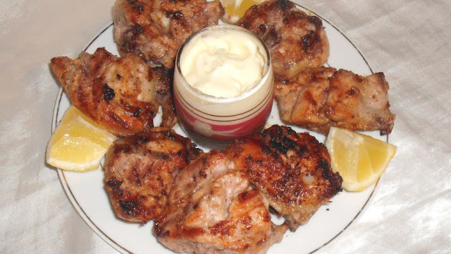Grilled Lebanese Garlic Chicken, garlic sauce and lemon slices in a plate