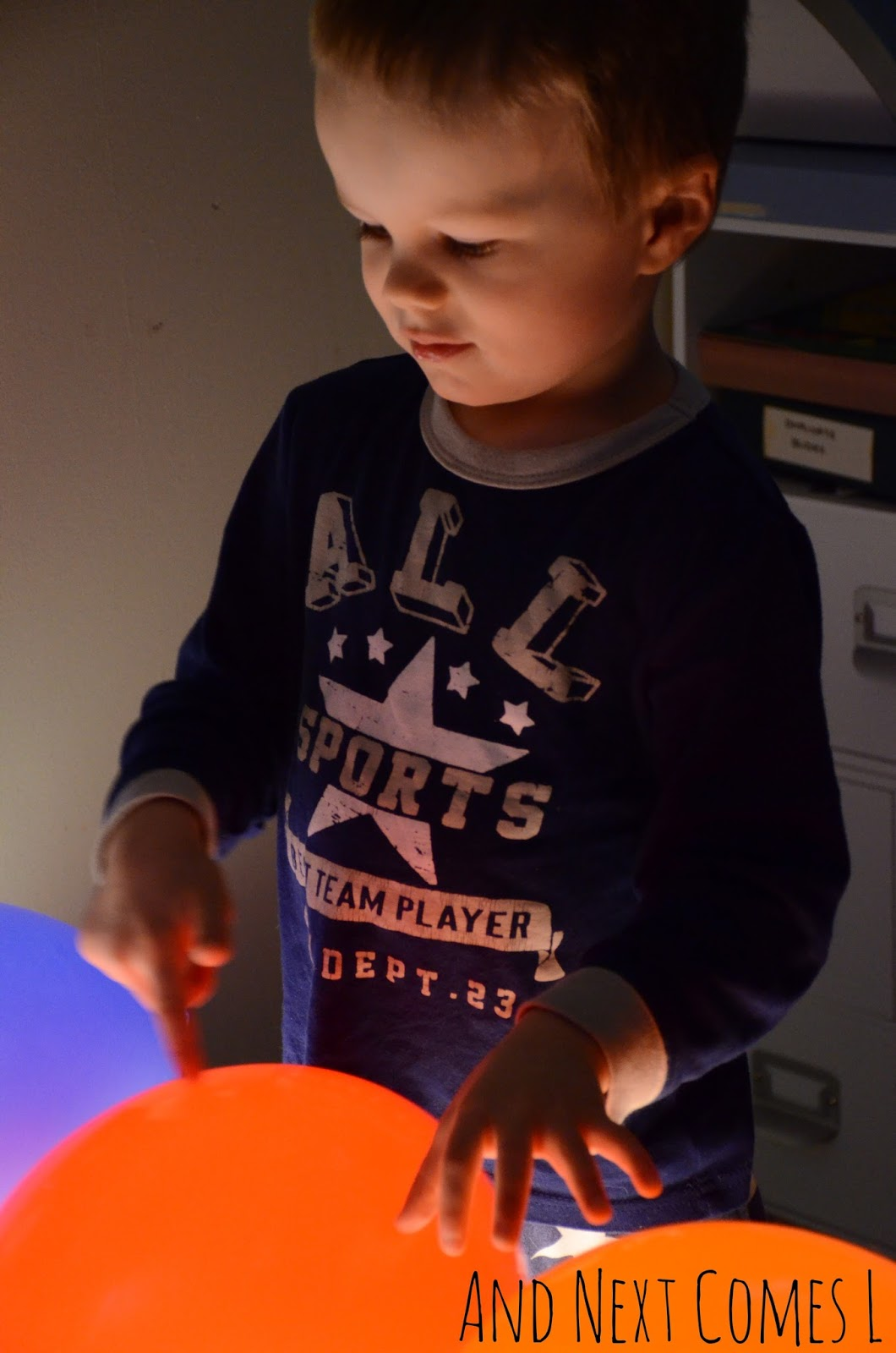 J checking out the balloons on the light table from And Next Comes L