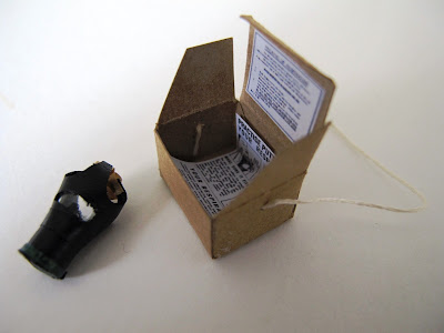 1/12-scale vintage gas mask and box containing instructions for use.