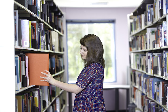 Student taking a book from a shelf in a Library