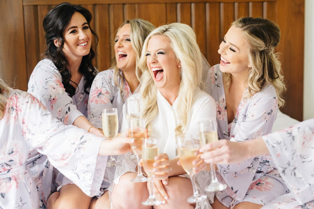 bride and bridesmaids celebrating with champagne and laughs