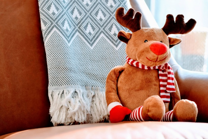 reindeer-soft-toy-on-brown-sofa-with-grey-blanket
