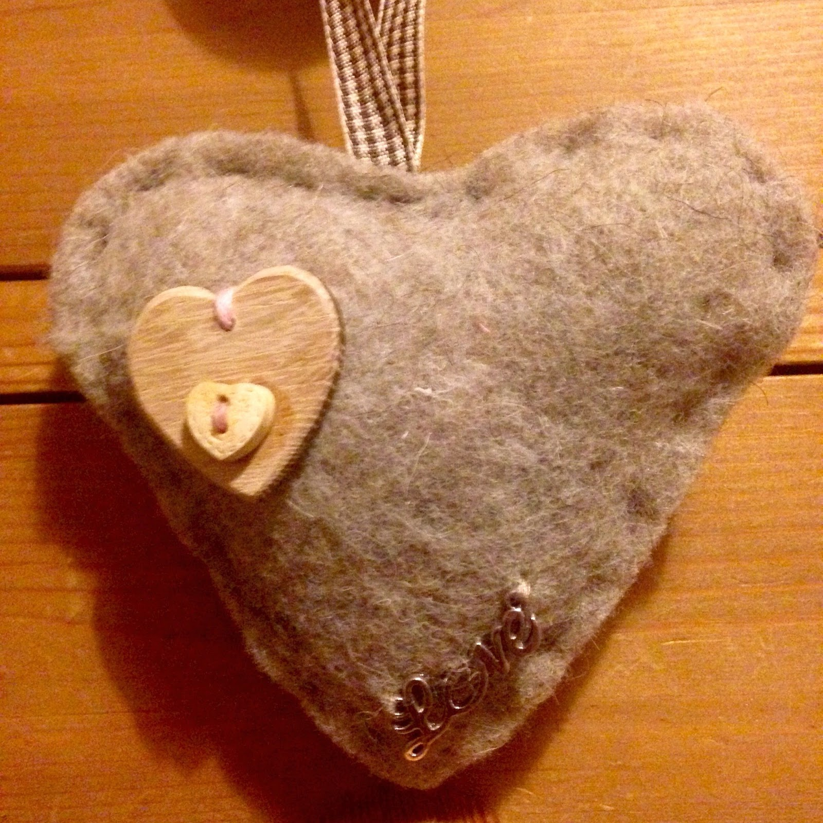 Cloth heart with button and love sewn on it
