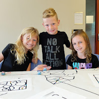 Three children code with Ozobots