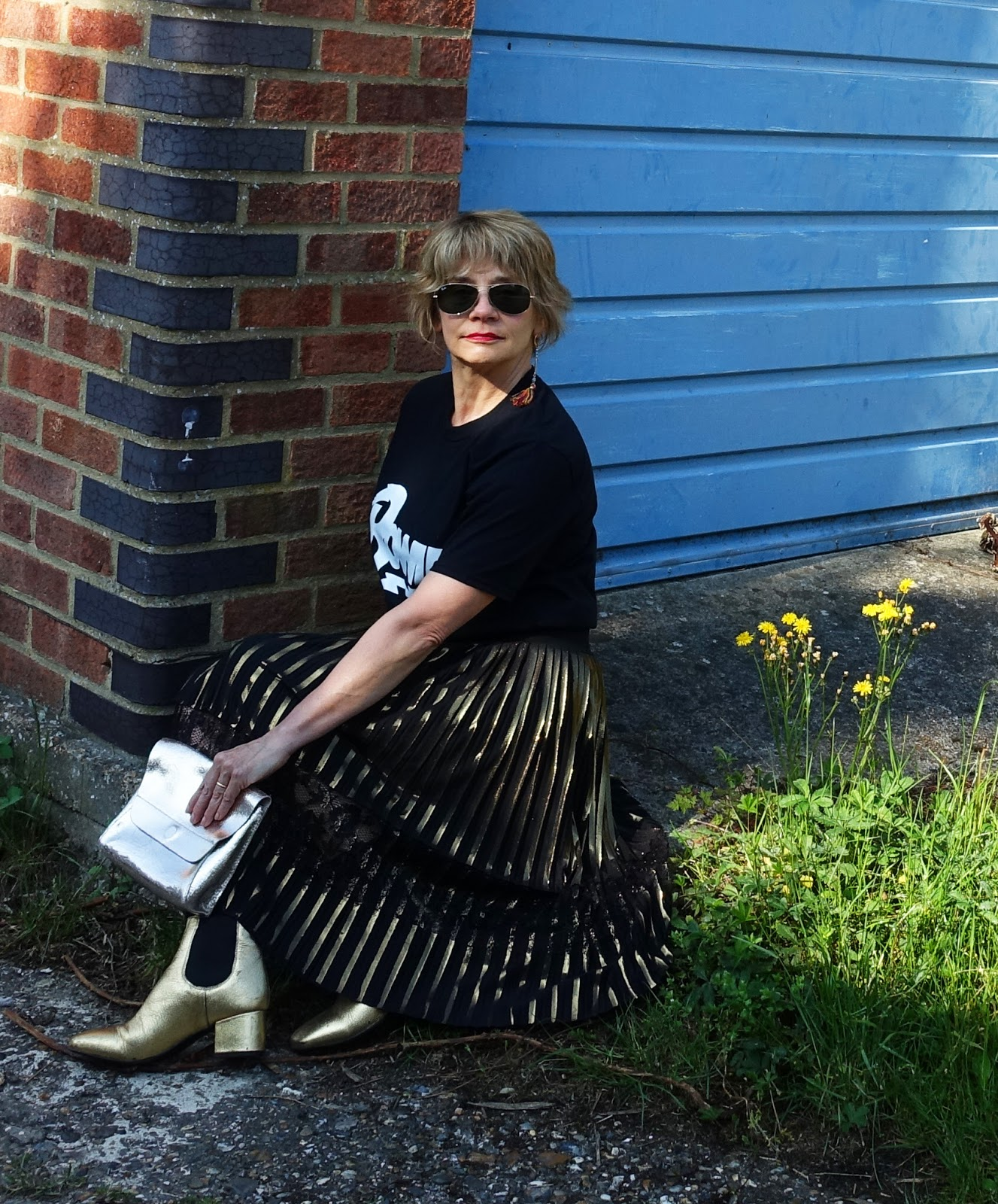 Image showing a fashion conscious over 45 woman wearing gold ankle boots with a gold and black pleated metallic skirt and black slogan t-shirt
