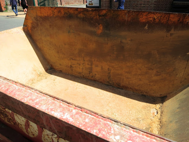 Empty skip, variously coloured and partly in shadow, with people wlaking away on other side of road.