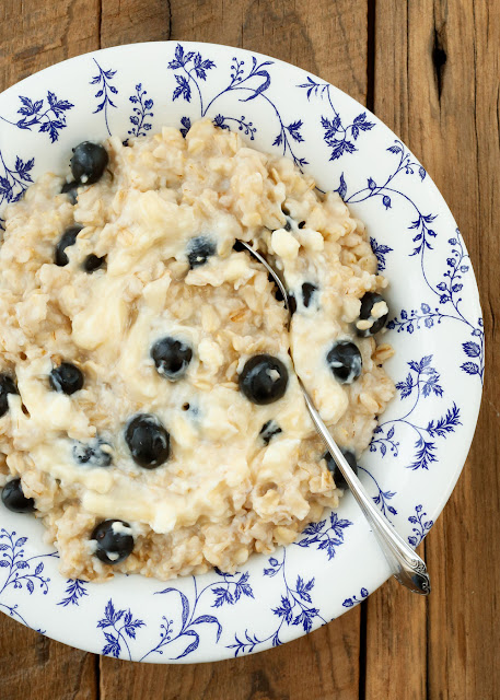 """Creamy oats, fresh blueberries, and a swirl of lightly sweetened """"cheesecake"""" adds up to Blueberry Cheesecake Oatmeal! - get the recipe at barefeetinthekitchen.com"""