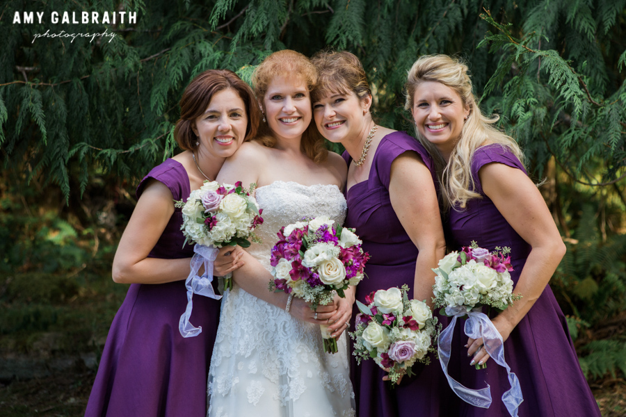 bridesmaids wearing purple dresses with bride