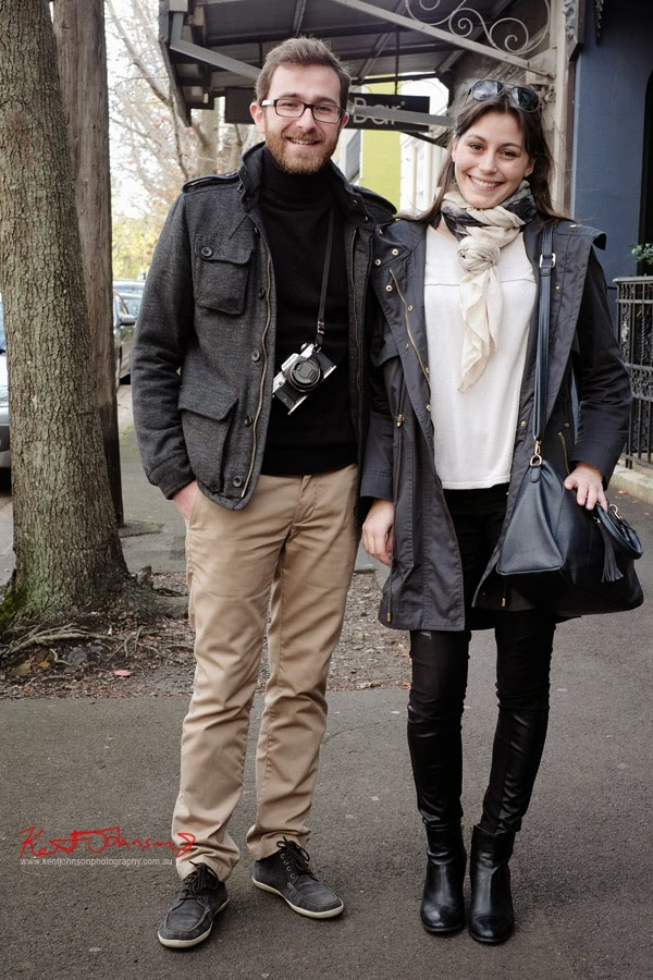 French couple Simon and Letitia in Queen Street Woollaraha, Street Style, Winter Jackets, Him - Turtle neck jumper, her -  knit tee with wound and knotted scarf leather leggings and boots.