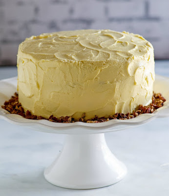 round maple cake on white pedestal