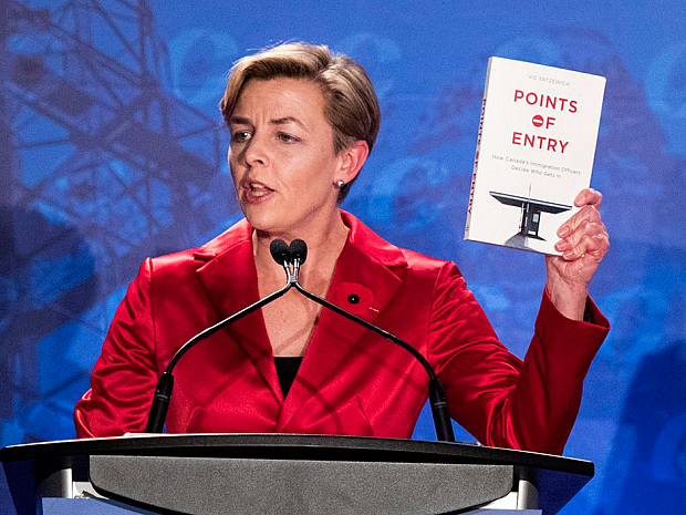 "Kellie Leitch holding a book, ""Points of Entry"" at the Conservative leadership debate"