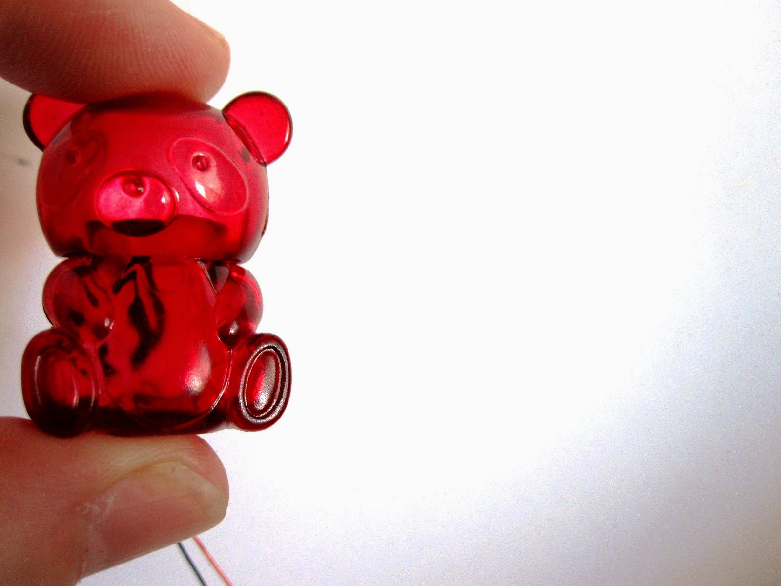 A miniature red plastic bear container held between two fingers.