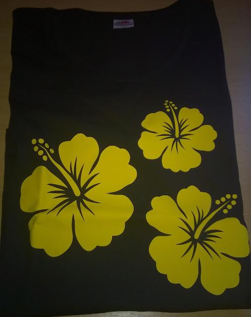 Gelbe Hibiskus Blüten auf schwarzem Shirt.