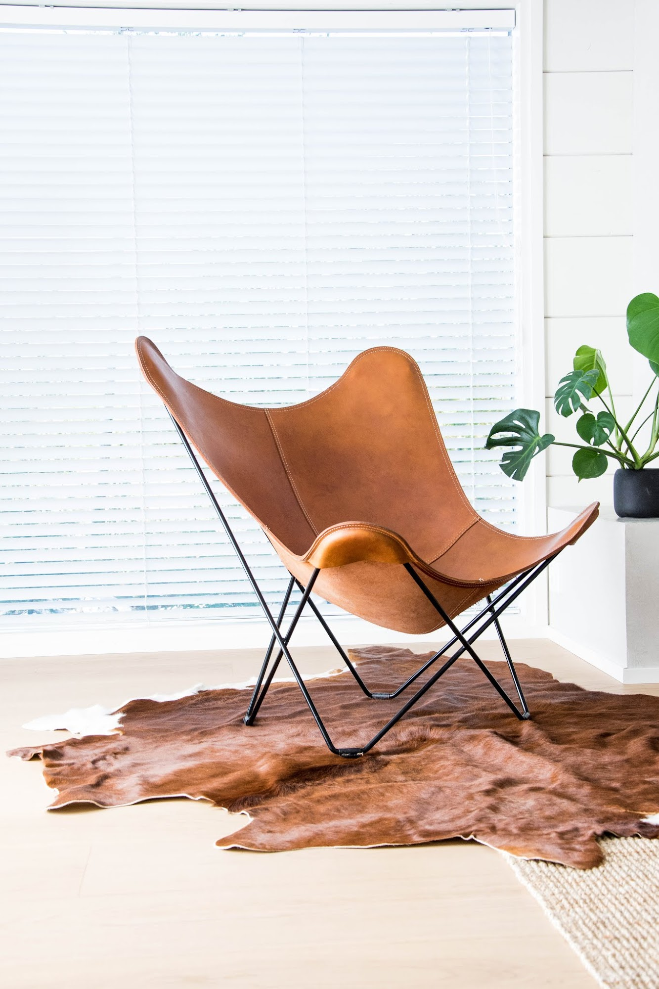 talo markki - lehmäntalja olohuoneessa - ruskea lehmäntalja - nahkainen lepakkotuoli - moderni hirsitalo - suomalaiset sisustusblogit
