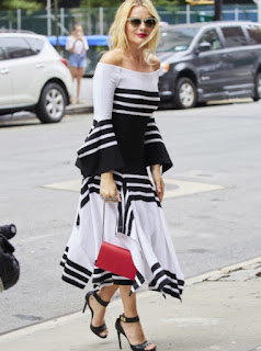 IMargot Robbie in Rosetta Getty black and white striped off the shoulder wide sleeve top and black and white striped ruffle maxi skirt
