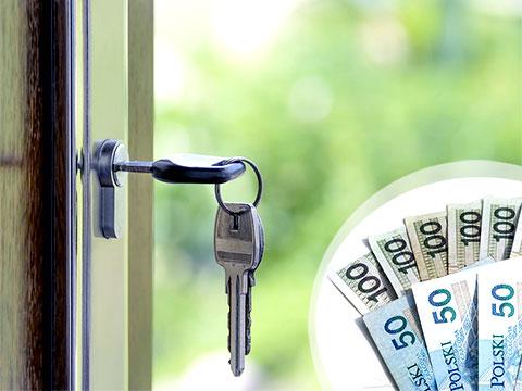 klucze wiszące w drzwiach i pieniądze za wynajem mieszkania