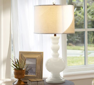 A white lamp next to a picture frame and small plant