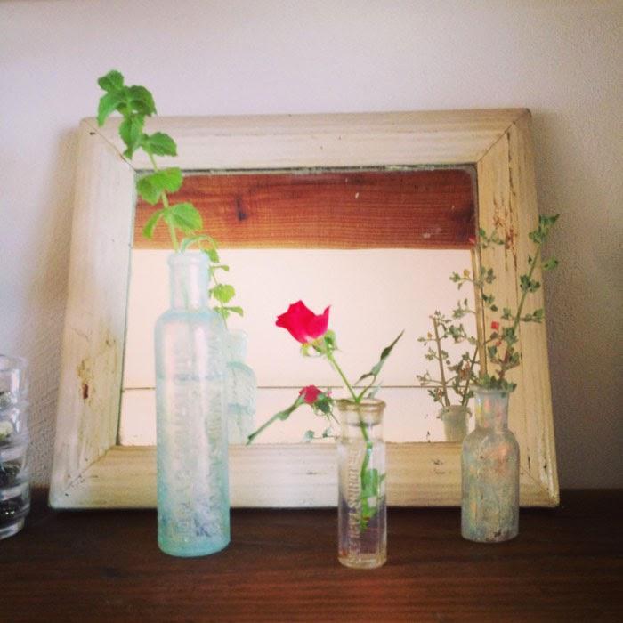 アンティークのガラスボトルにミニバラの花を活けてアンティークミラーに映す