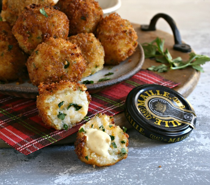 Crispy mustard coated fried potato balls with cheese.