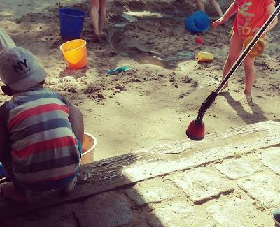 Spielende Kinder im nassen Spielplatzsand