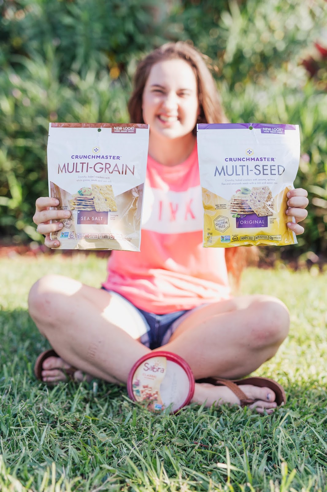 girl in victoria's secret pink tee holding Crunchmaster multi-grain and multi-seed crackers with Sabra classic hummus dip