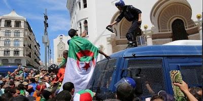"""بالفيديو/ متظاهران يلقيان بـ""""شرطي"""" من أعلى عربة أمنية في الجزائر"""
