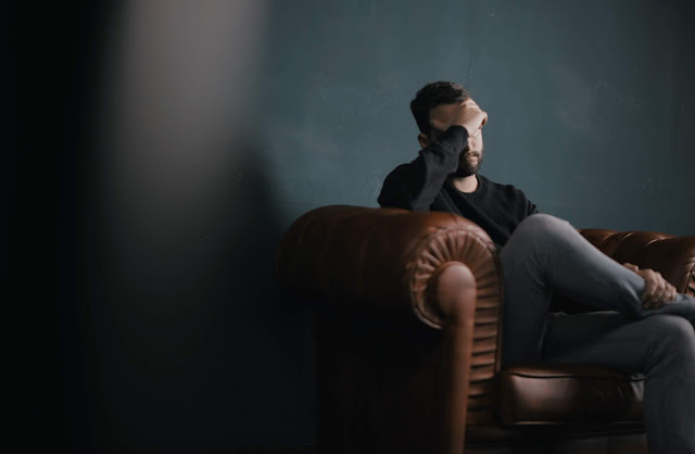 Bearded man sitting on a leather couch with his head leaning against one of his hands