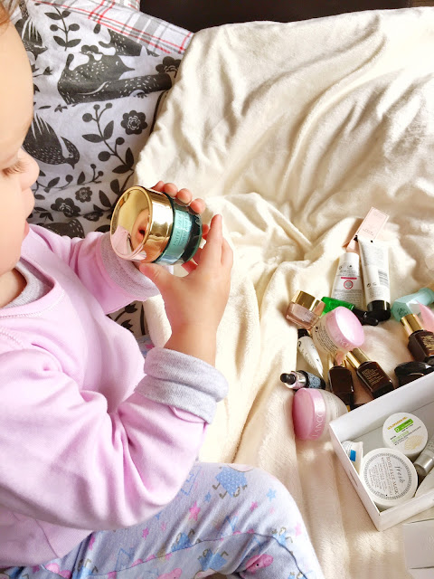 baby girl looking at makeup jar