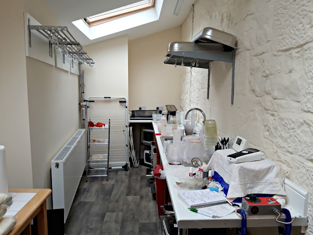 Peak District Yarns dye studio.  To the left is a radiator and above that chrome drying racks.  To the right is a long worktop and stainless steel sink.  Stainless steel basins are stacked above the sink