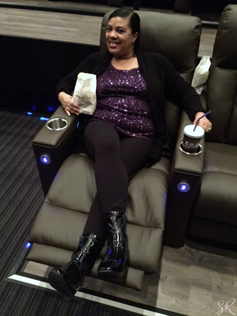 woman lounging in leather theater seat