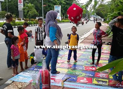 ULAR TANGGA  :  Mba Asih Maulida dari Pontianak Post menilai ketrampilan anak anak itu bermain ular tangga.  Seru.  Foto Asep Haryono/www.simplyasep.com