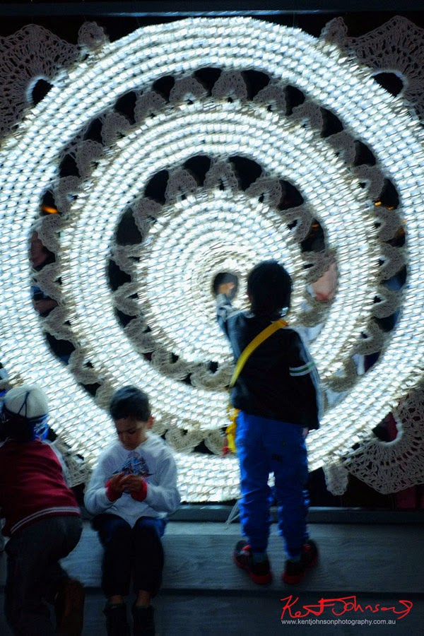 Children interact with the large illuminated crochet artwork Magic Circle by Tina Fox. Bennalong Point, Circular Quay Vivid 2014.