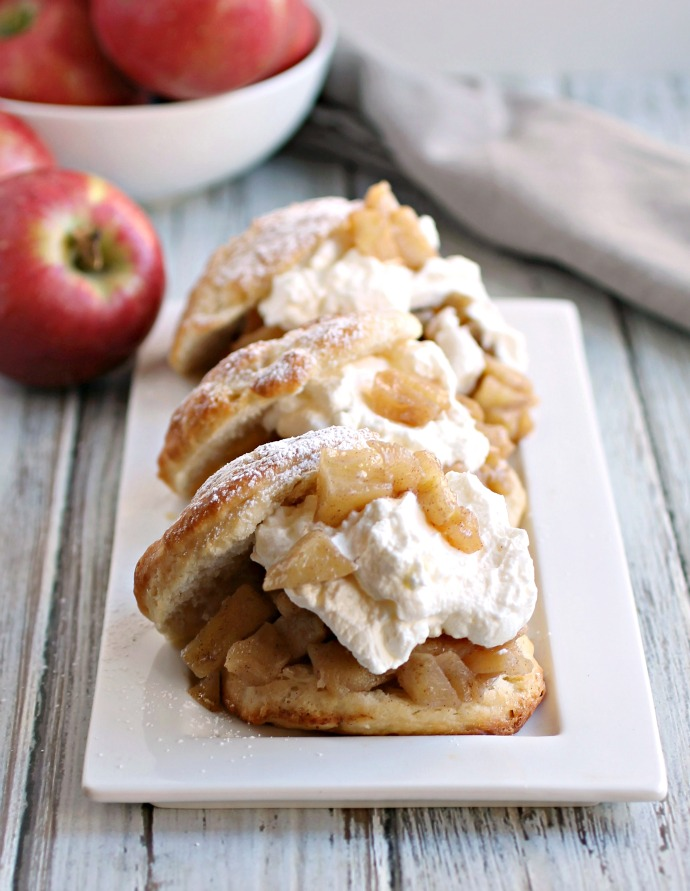 Recipe for sweet sauteed apples served on a sweet biscuit and topped with fresh whipped cream.