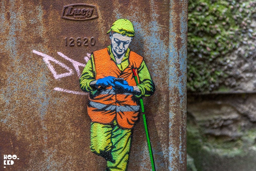 Miniature stencil of city worker on a phone by artist Jaune in Belgium