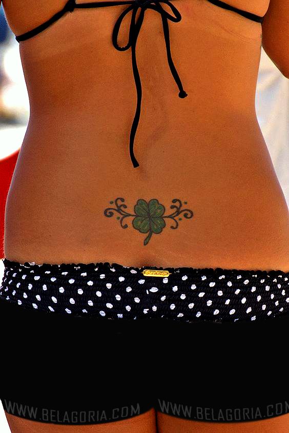 chica en la playa, va en bañador, lleva un tatuaje de trebol en la espalda baja