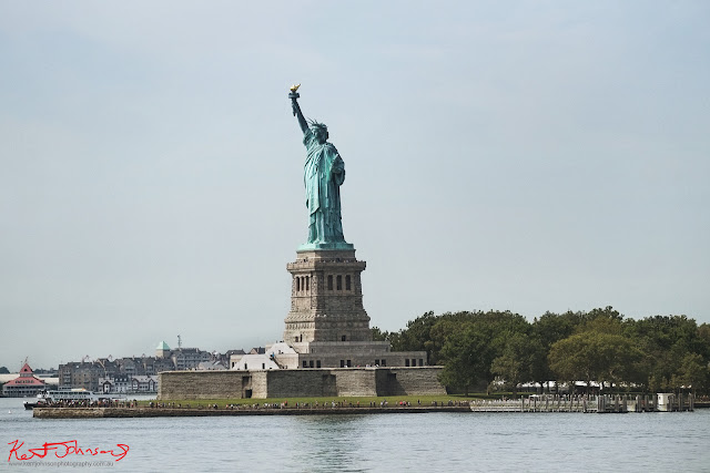 The famous Statue of Liberty as seen from the passing Staten Island Ferry.  Travel photography by Kent Johnson.