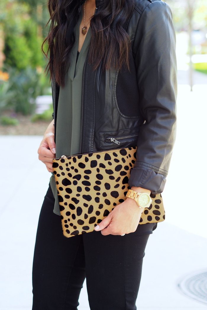 olive top + black moto jacket + leopard print clutch