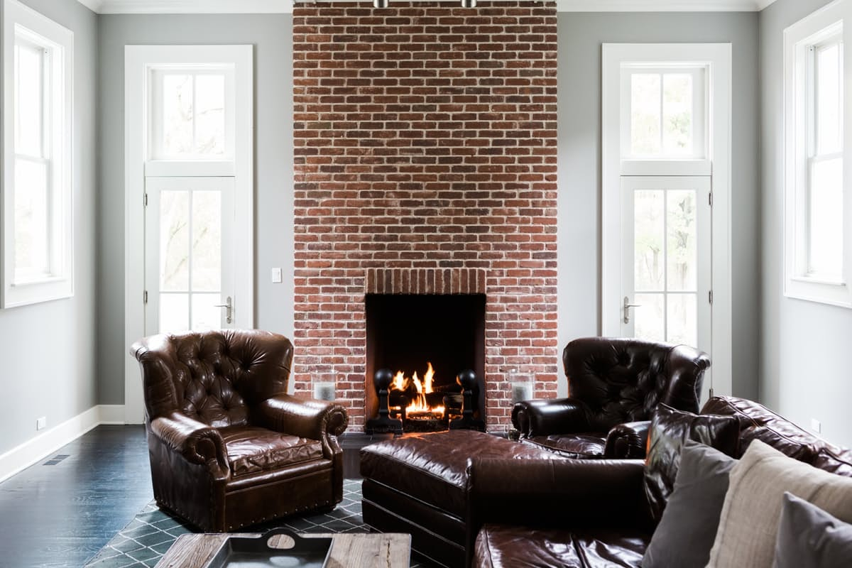 Modern farmhouse great room with red exposed brick fireplace on Hello Lovely Studio